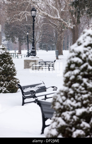 Recent snow fall covers trees, park benches and drinking fountains in Victoria Park. - Stock Image