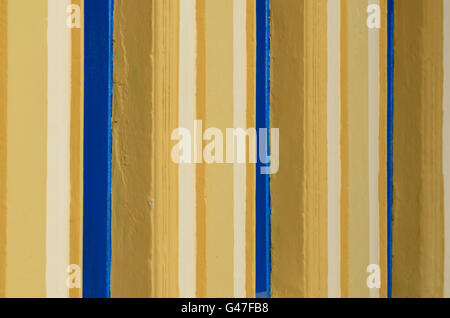 yellow and blue vertical patterns painted on a wall - Stock Image