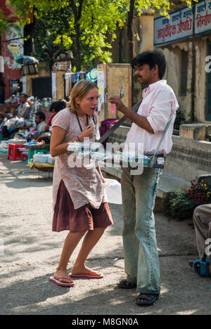 Exchange between a female tourist and a street vendor in the town of  Rishikesh, beside the sacred Ganges River, - Stock Image