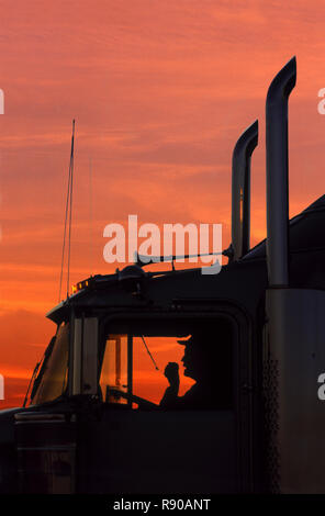 A shiloiuette of a truck driver on his CB radio in the cab of his Class 8 truck tractor. - Stock Image