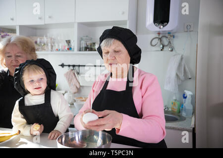 Family eating pancakes and drinking tea in the kitchen - Stock Image