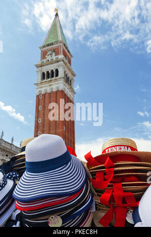 Souvenir hats for sale in St. Mark's Square with the Campanile in the background; Venice, Italy - Stock Image