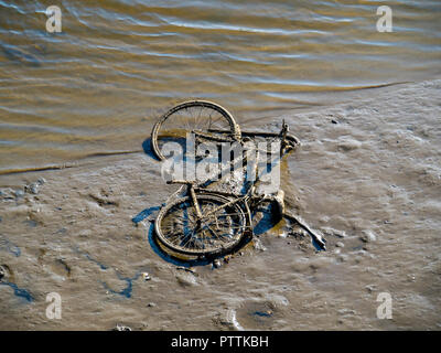 Old bicycle thrown into a tidal river exposed lying on the soft mud at low tide - Stock Image