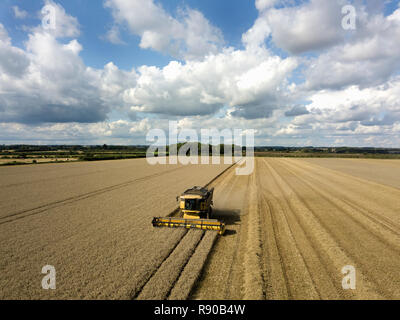 A drone shot of fields in a farming landscape, and a combine harvester working harvesting a crop. - Stock Image