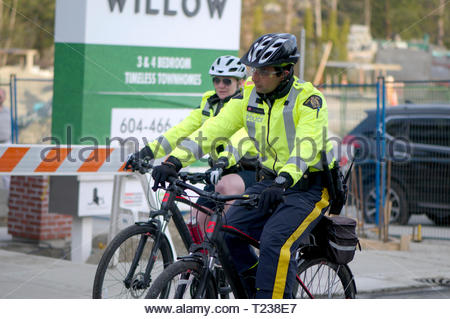 Two RCMP officers on bicycles patrolling a media event at a townhouse in Maple Ridge, B. C - Stock Image