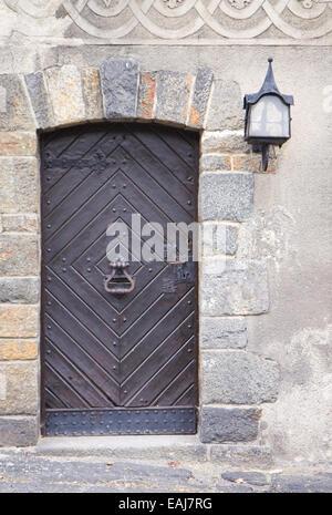 Old wooden medieval door with steel knocker - Stock Image