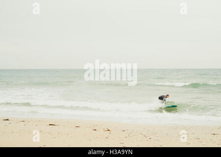 A surfer at Gyllyngvase Beach, Falmouth, Cornwall - Stock Image