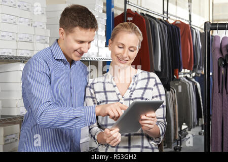 Couple Running On Line Fashion Business In Warehouse - Stock Image