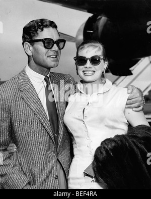 Swedish actress Anita Ekberg with her husband, British actor Anthony Steele, arriving at London Airport in 1956. - Stock Image