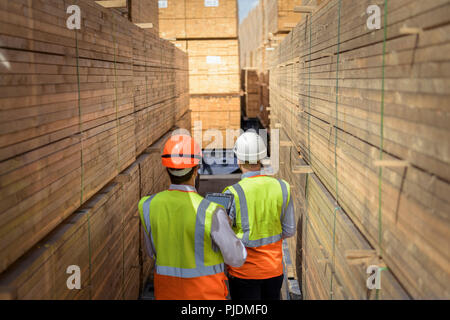 Workers among stacks of timber in storage at port - Stock Image