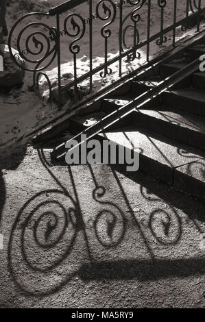 An old-fashioned metal handrail with a contrasting shade left by the sun. Tartu, Estonia. - Stock Image