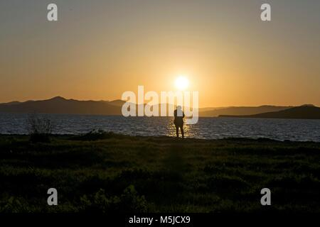 A woman looks at the sunset near Oakland, CA - Stock Image