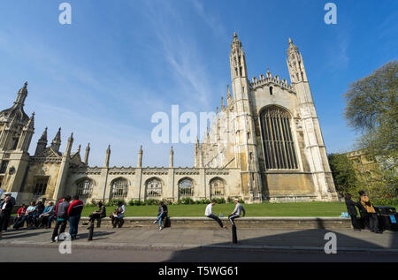 Tourists resting on wall in front of Kings College Chapel - Stock Image
