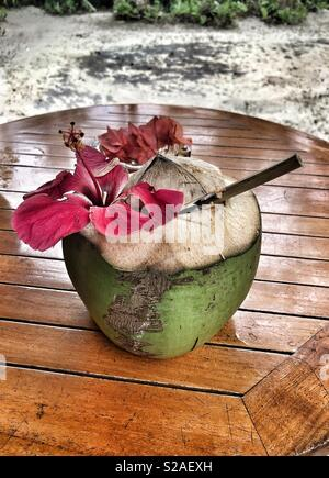 A coconut drink with a bamboo straw on a round wooden table - Stock Image