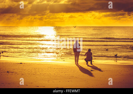 Sunset on beach in Domburg with couple taking pictures - Stock Image