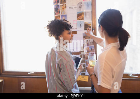 Creative female designers reviewing photographs - Stock Image