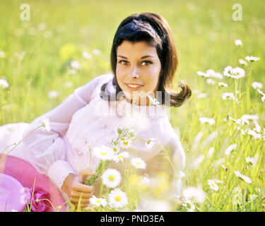 1970s SMILING FRESH PRETTY BRUNETTE WOMAN LYING OUTDOOR IN DAISY FIELD  WEARING PINK SPRING DRESS LOOKING AT CAMERA - kg5875 PHT001 HARS GROWNUP HEALTHINESS NATURE COPY SPACE HALF-LENGTH LADIES PERSONS GROWN-UP DAISY SUMMERTIME EYE CONTACT BRUNETTE DAISIES FRESH PRETTY HAPPINESS CHEERFUL SUMMER SEASON LIPSTICK FEMININE SMILES JOYFUL STYLISH PEOPLE ADULTS SPRINGTIME YOUNG ADULT WOMAN CAUCASIAN ETHNICITY OLD FASHIONED - Stock Image