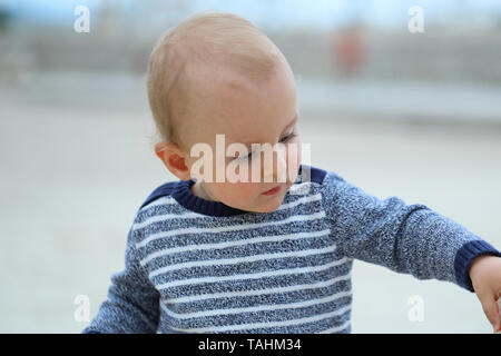 Beautiful Blond Baby Boy Wearing A Blue And White Sweater On The Sandy Beach, Close Up Portrait - Stock Image