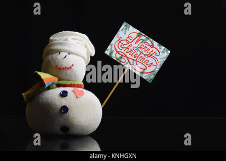 """Snowman figure holding a paperboard sign on a stick with text """"Merry Christmas!"""" written on it, and surrounded with - Stock Image"""