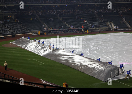 Citi Field grounds crew rolling the tarp on the field after a rain delay, Queens, NY, USA - Stock Image