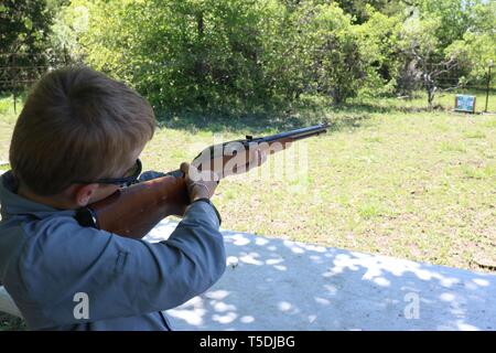 Young boy doing target practice with a rifle - Stock Image
