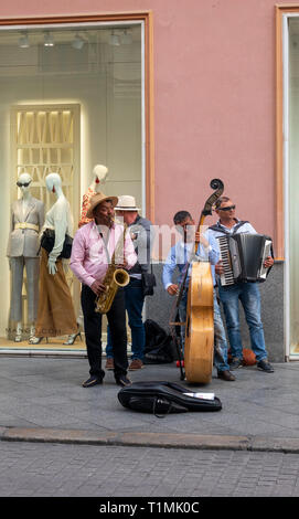 A buskers band playing on a street in Seville - Stock Image
