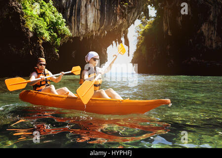 Couple of kayakers swims under the cliff in sea - Stock Image