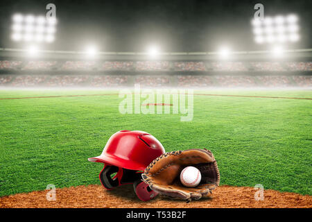 Baseball helmet, glove and ball on field at brightly lit outdoor stadium. Focus on foreground and shallow depth of field on background and copy space. - Stock Image