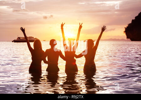 Four happy friends are meeting sunset at sea beach standing in water and hugging with raised arms - Stock Image