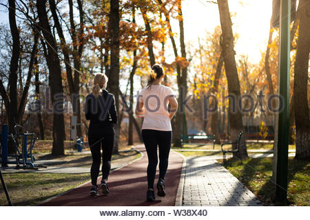 Two beautiful fit women running in parks during fall and sunset - Stock Image