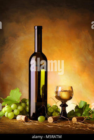 Still life with wine bottle, glass, grapes and vine leaves - Stock Image