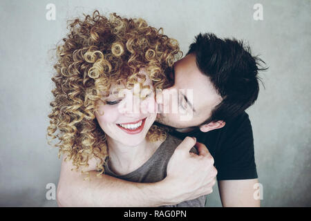 Portrait of a natural caucasian couple of young woman with curly blonde hair and man. He kisses her and she looks happy and smiles - Stock Image