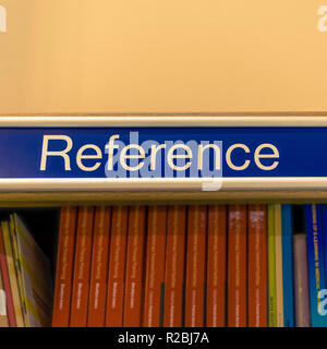 Reference sign above shelf full of books in library - Stock Image