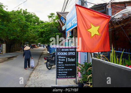 A Vietnamese flag hangs outside a tourist agent on a quiet street in the coastal town of An Bang, Central Vietnam. The town is situated near the UNESC - Stock Image
