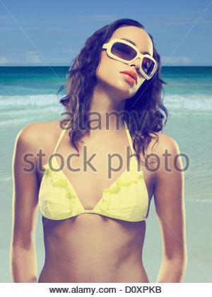 Young woman wearing yellow bikini and sunglasses - Stock Image