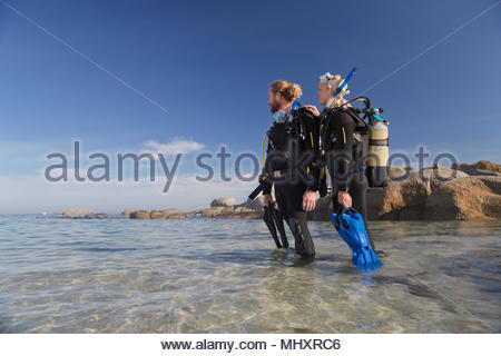 Couple in wetsuits going ocean scuba diving from beach - Stock Image