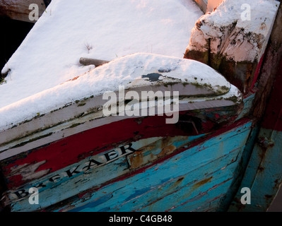 An abandoned and decaying boat with a sprinkling of snow - Stock Image
