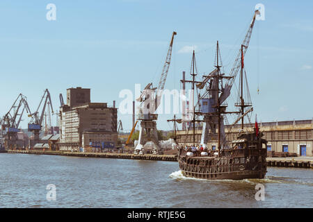 tourists on mock pirate ship sailing on the Martwa Wisla river through the shipyards in Gdansk, Poland, Europe - Stock Image