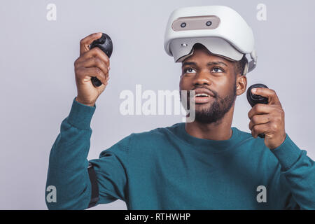 Young excited African man being full of impressions after first experience of virtual reality game. Cheerful male gamer with vr glasses on head, holds - Stock Image