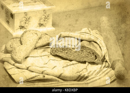 Bread loaf wrapped in a kitchen towel, rolling pin, and two slices of bread lying on the cloth. Decoupage box is - Stock Image