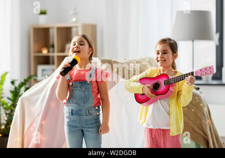girls with guitar and microphone playing at home - Stock Image