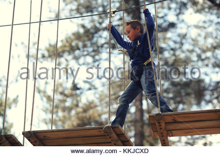 boy walking across high ropes - Stock Image