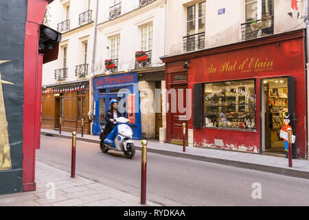 Scooter passing through Rue Guisarde in the 6th arrondissement of Paris, France. - Stock Image