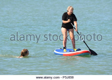 Littlehampton, UK. Wednesday 27th June 2018. A paddleboarder takes to the sea on another very warm and sunny morning in Littlehampton, on the South Coast. Credit: Geoff Smith / Alamy Live News. - Stock Image