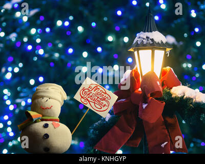 """Snowman figure holding a placard board. Text """"Merry Christmas!"""" written on it. Street lantern wrapped in red ribbon - Stock Image"""