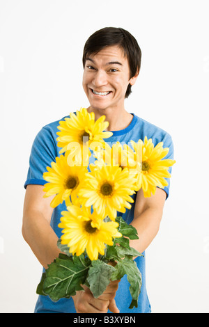 Asian young man holding bouquet of yellow gerber daisies smiling - Stock Image