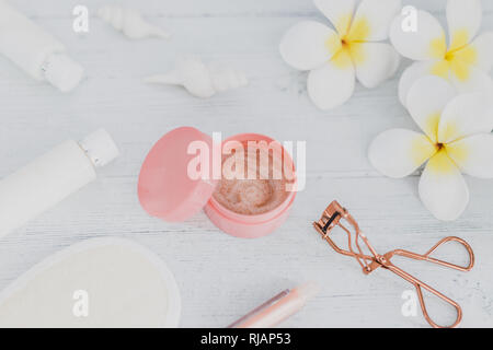 spa inspired set of scrub body lotions with make-up details such as lash curler and lipgloss surrounded by flowers and seashells on light coloured woo - Stock Image
