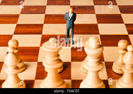 miniature figurine of a businessman on a chessboard - Stock Image