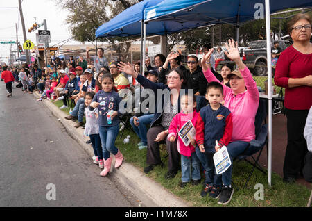 Multi-generational crowd watches from sidewalk as the annual Washington's Birthday Celebration parade passes by in Laredo, Texas. - Stock Image