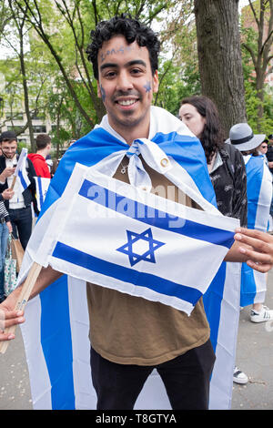 Posed portrait of an NYU student who is wearing & holding an Israeli flag. At the Israel Independence Day celebration in Washington Square Park, NYC - Stock Image